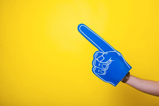 Photo of a handsome arm,  wearing a big blue fan glove, over isolated yellow background Photo of a handsome arm,  wearing a big blue fan glove, over isolated yellow background baseball sport stock pictures, royalty-free photos & images