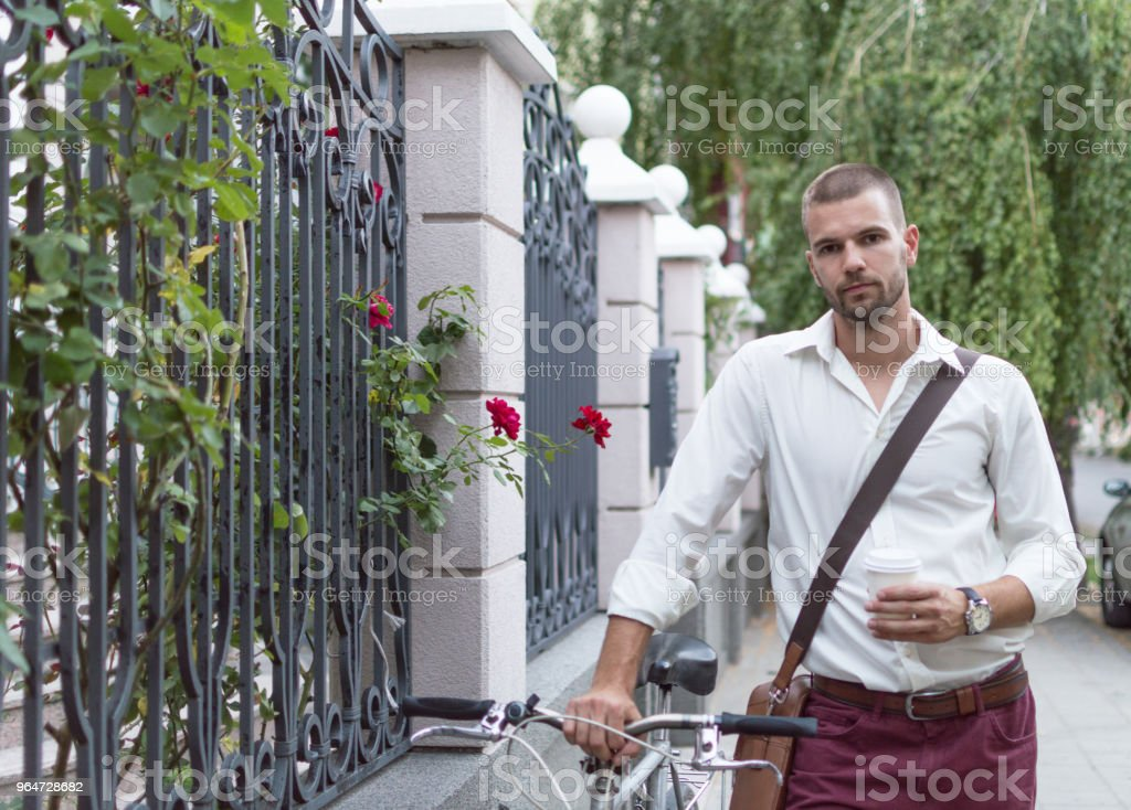 Photo of a handsome man leading his bike royalty-free stock photo