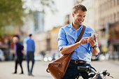Photo of a handsome man with bike using smartphone