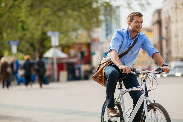 photo of a handsome smiling man riding bike in city - bisiklet stok fotoğraflar ve resimler