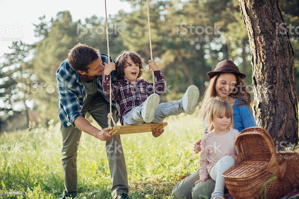 Photo of a happy family enjoying fun time in forest stock photo