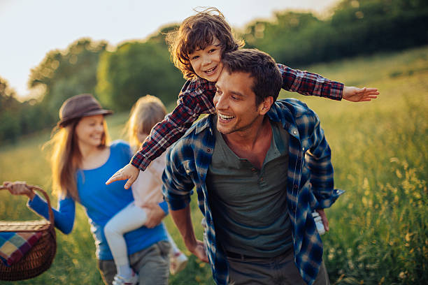 Photo of a happy family going for picnic Picture of a young family going for a picnic, walking together threw high grass with the sun in their back. piggyback stock pictures, royalty-free photos & images