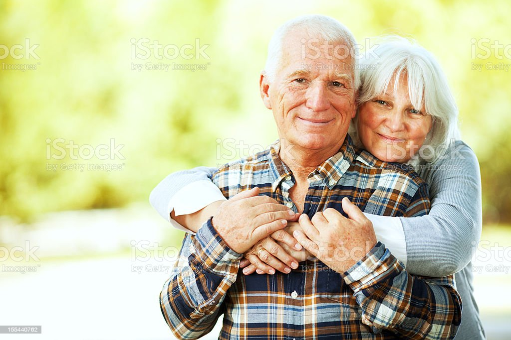 Photo of a happy hugging senior couple in park stock photo