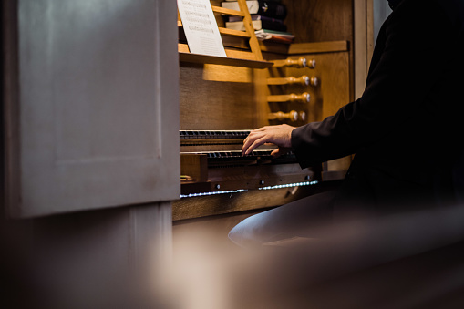 photo of a man playing piano in a church