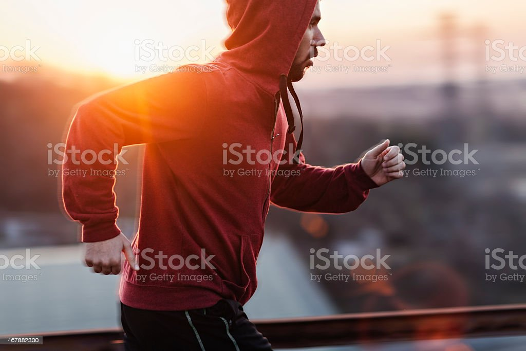 Photo of a man running while sun is setting stock photo