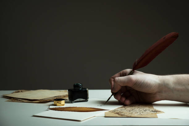photo of a man's hand writing letter with antique pen and old papers and inkwell on the table - quill stock photos and pictures