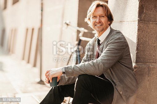 Picture of a smiling mature man having take away coffee while sitting on the stairs by the road