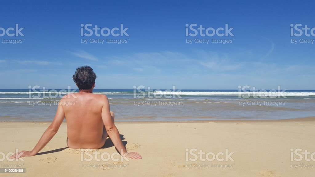 photo of a naked man sitting alone on the beach stock photo