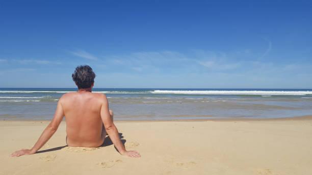 foto von einem nackten mann sitzt allein am strand - fkk strand stock-fotos und bilder