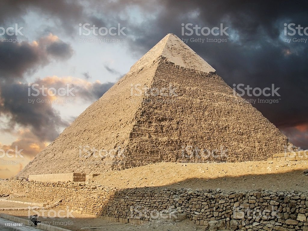 Photo of a pyramid in Giza showing stormy clouds above royalty-free stock photo