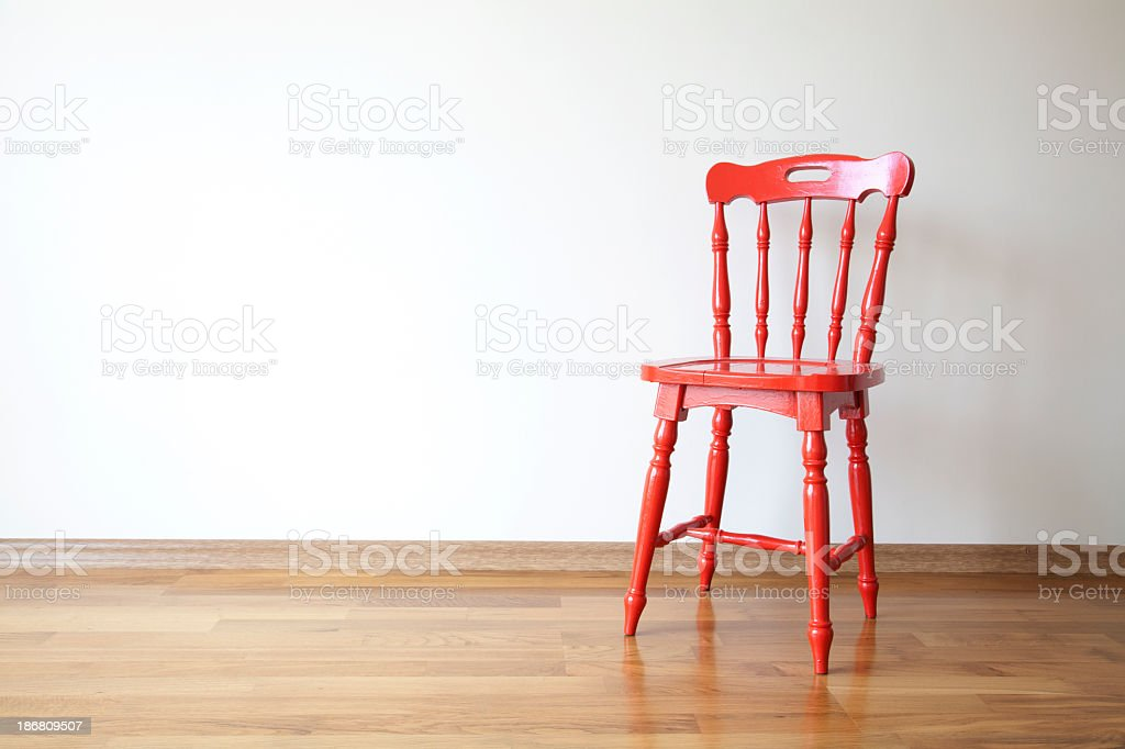 Photo of a red wooden chair in front of a blank wall royalty-free stock photo