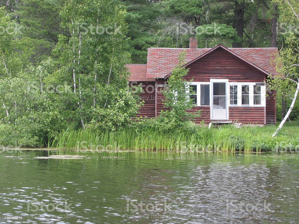 Photo of a rustic lakeshore cabin with a lake royalty-free stock photo