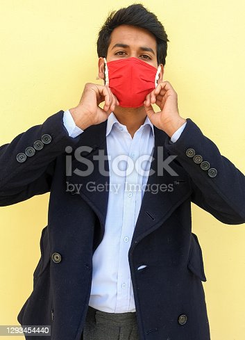 Photo of a smart man adjusting his coronavirus mask during lockdown with yellow color background