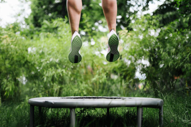 photo of a sport woman jumping on a trampoline stock photo