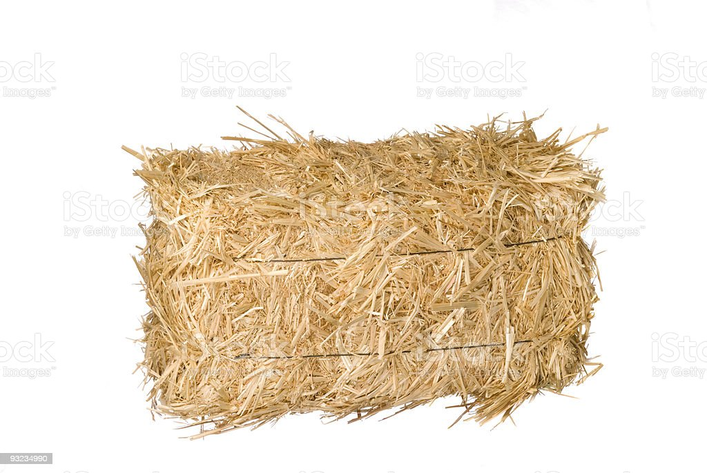 A photo of a square bale of dry hay on a white background stock photo