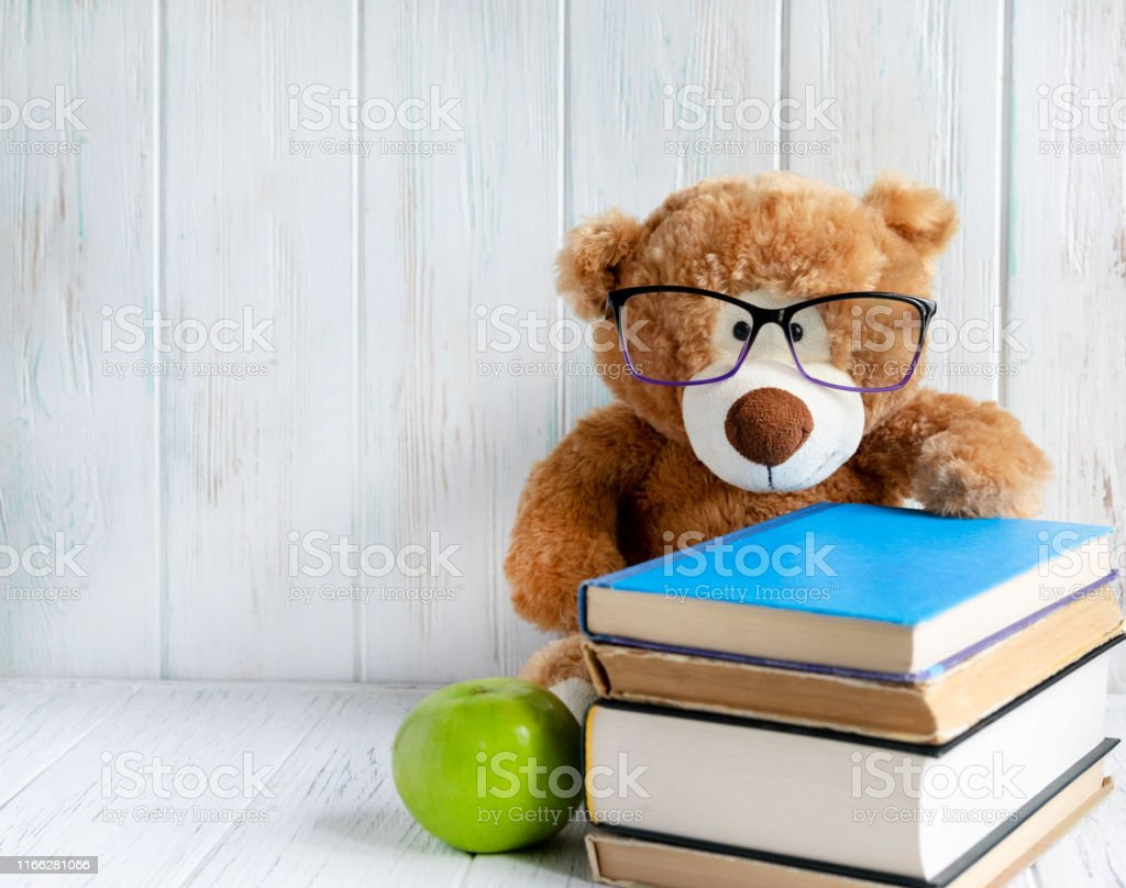 Photo of a stack of books with a bear, an apple and a place for an...