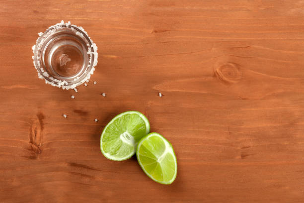 A photo of a tequila shot with lime wedges, shot from above on a rustic background with a place for text A photo of a tequila shot with lime wedges, shot from above on a rustic background with a place for text tequila shot stock pictures, royalty-free photos & images