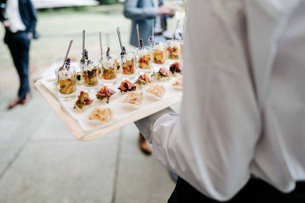 photo of a waiter holding snacks at a wedding stock photo