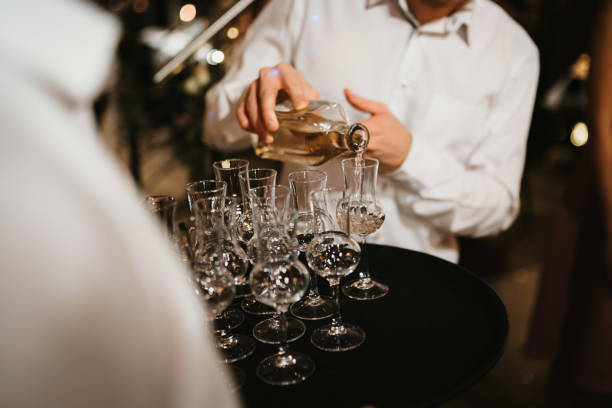 photo of a waiter seving alcohol in glasses stock photo