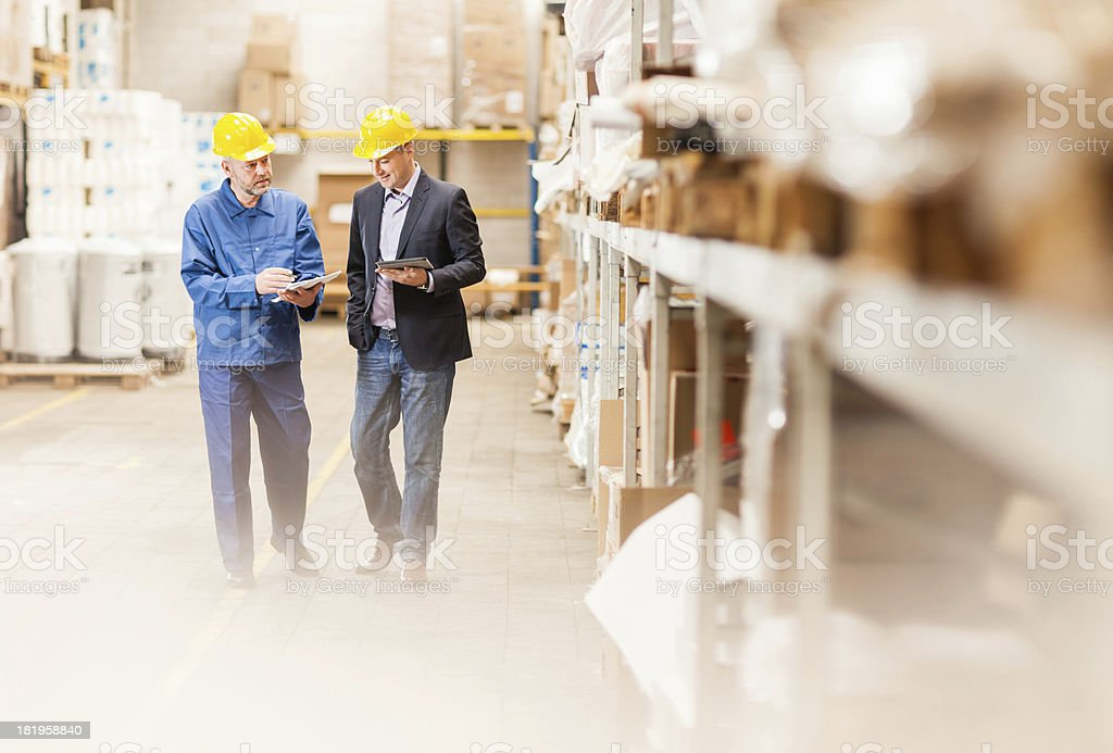 Photo of a warehouse manager and worker walking in warehouse stock photo