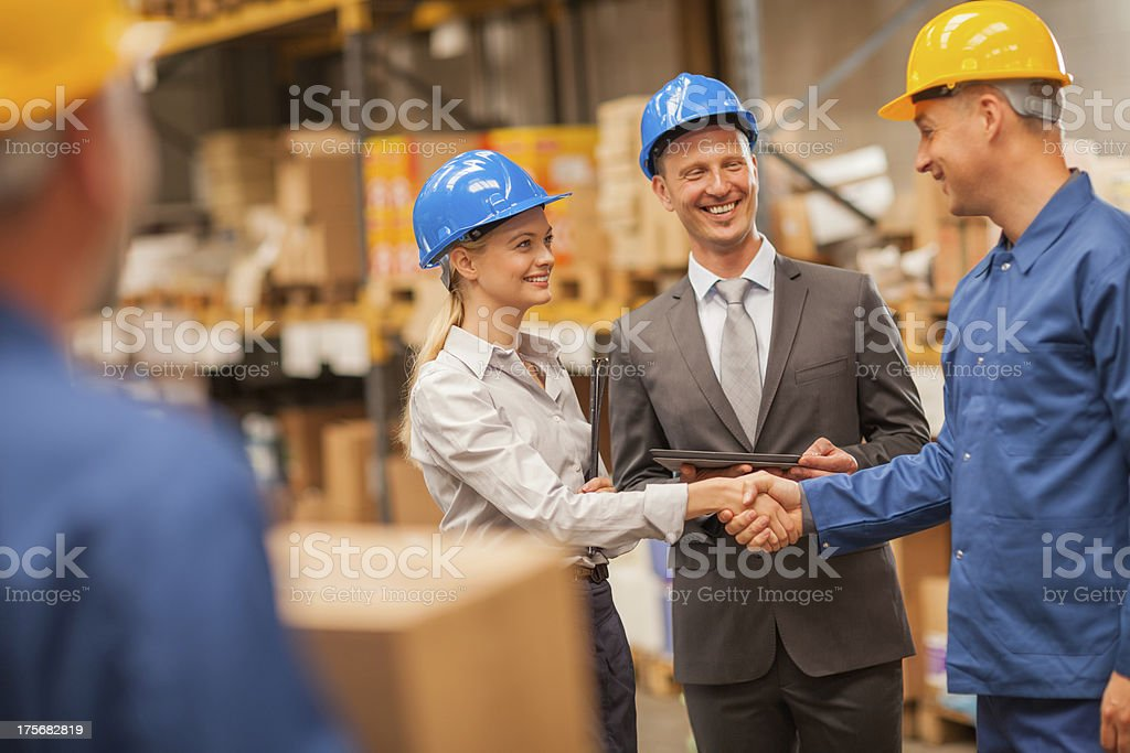 Photo of a warehouse manager shaking hands with worker royalty-free stock photo