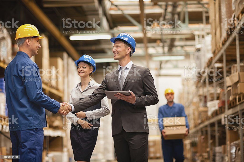 Photo of a warehouse manager shaking hands with worker stock photo