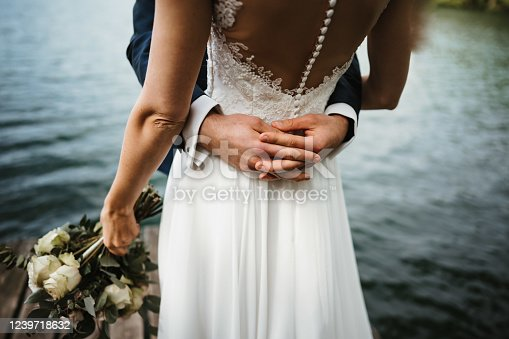 a wedded couple at a lake