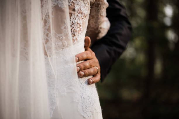 photo of a wedded couple standing in nature stock photo