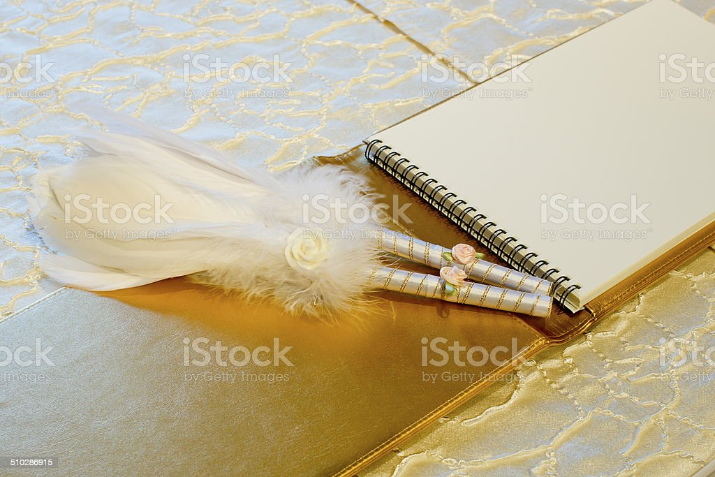 Photo of a wedding register and feather pen. Wedding guestbook. stock photo