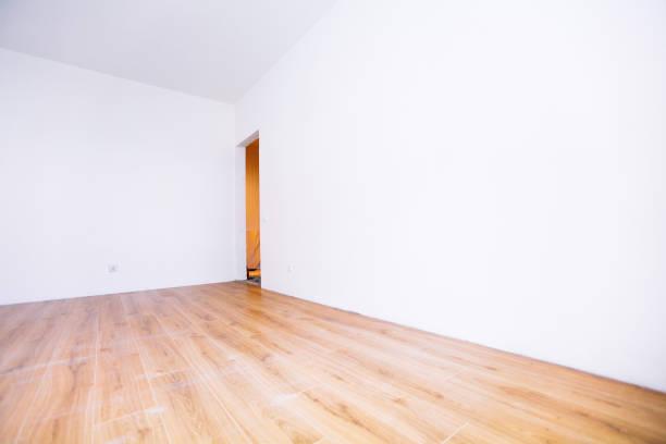 Foto eines weißen, leeren skandinavischen Zimmers mit Holzboden und Wänden. – Foto