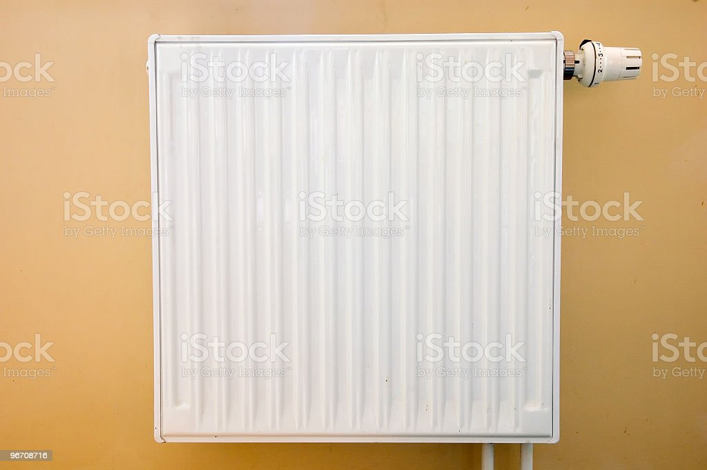 A photo of a white radiator attached to a brown painted wall royalty-free stock photo