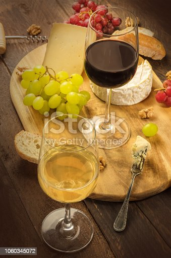 508216406 istock photo A photo of a wine and cheese tasting. Glasses of red and white wine with bread and grapes on a dark rustic wooden background 1060345072