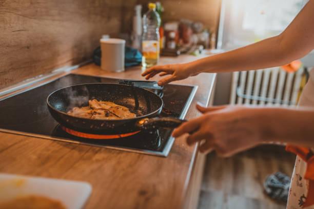 foto einer frau, die in der küche kocht - scharf anbraten stock-fotos und bilder