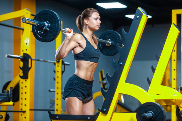 Photo of a woman holding weight while working out with barbell in a gym. Muscles woman showing sixpack abs stock photo