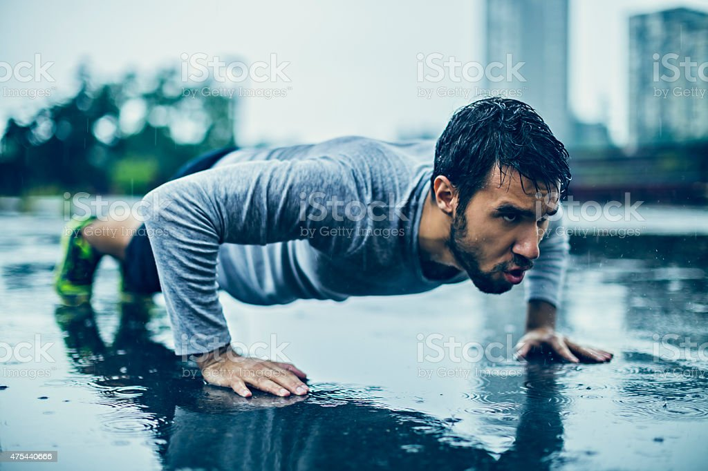 Photo of a young athletic man exercising in the rain stock photo