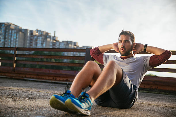 photo of a young athletic man exercising outdoors - sit ups stock photos and pictures