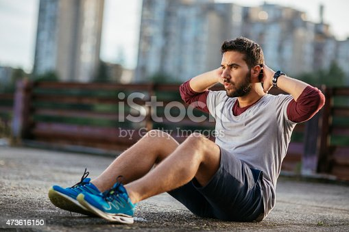 Picture of a young athletic man out exercising. He is sitting on the rough path underneath a blue sky doing sit-ups. In the background are a brown fence and some city buildings.