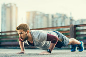 Picture of a young athletic man doing push-ups outdoors