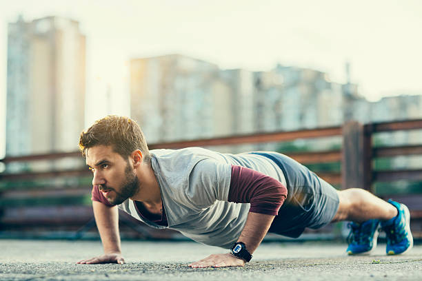 photo of a young athletic man exercising outdoors - push up stock photos and pictures