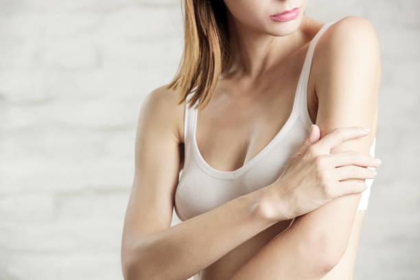 Foto einer jungen attraktiven Frau, die ihren Arm, ihr trockenes oder dehydriertes Hautpflegekonzept berührt, ist – Foto