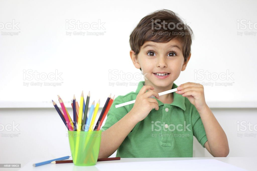 Photo of a young boy with a cup of pencil crayons stock photo