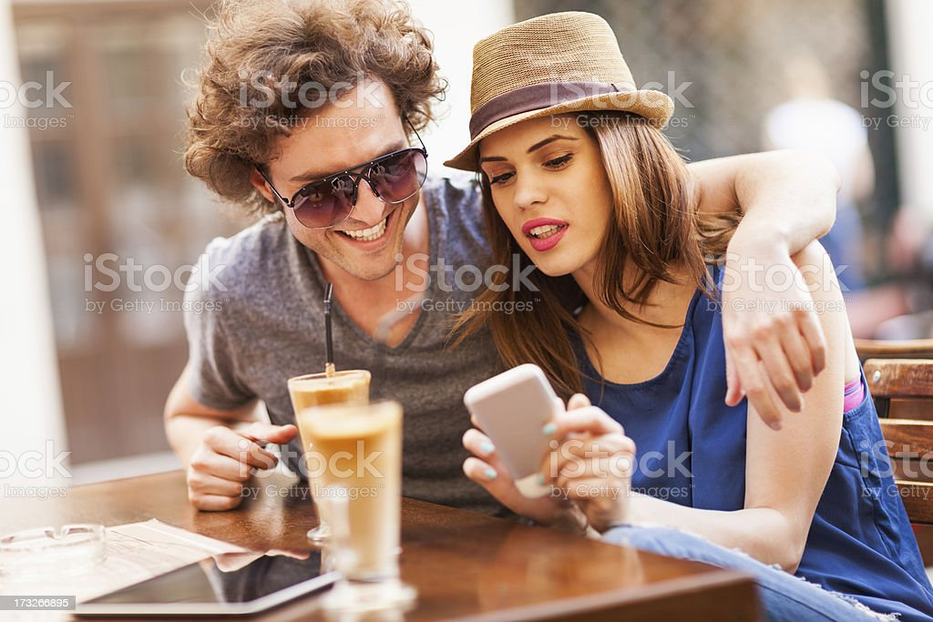 Photo of a young couple looking at smartphone in cafe royalty-free stock photo