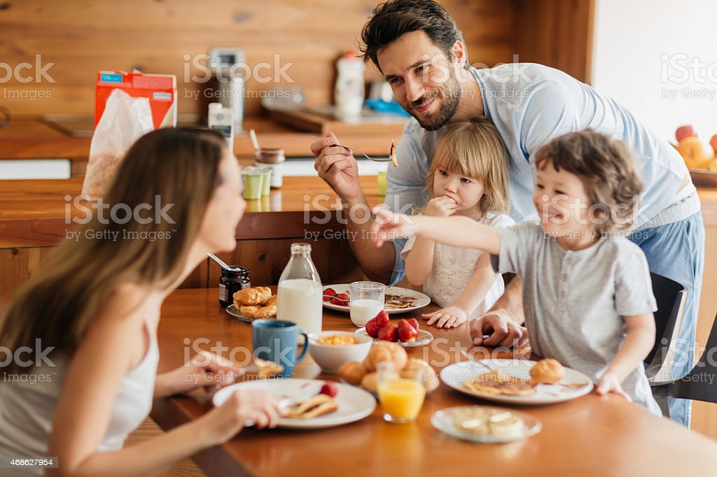Photo of a young happy family having breakfast stock photo