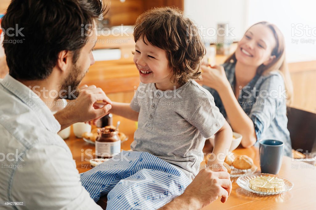 Photo of a young happy family having breakfast royalty-free stock photo