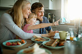 Picture of a young happy family surfing the net while having breakfast