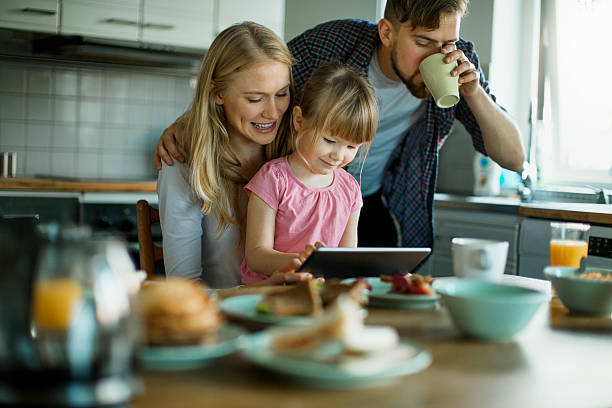 photo of a young happy family having breakfast - eating technology stock photos and pictures