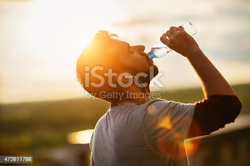 istock Photo of a young man drinking water 472611766