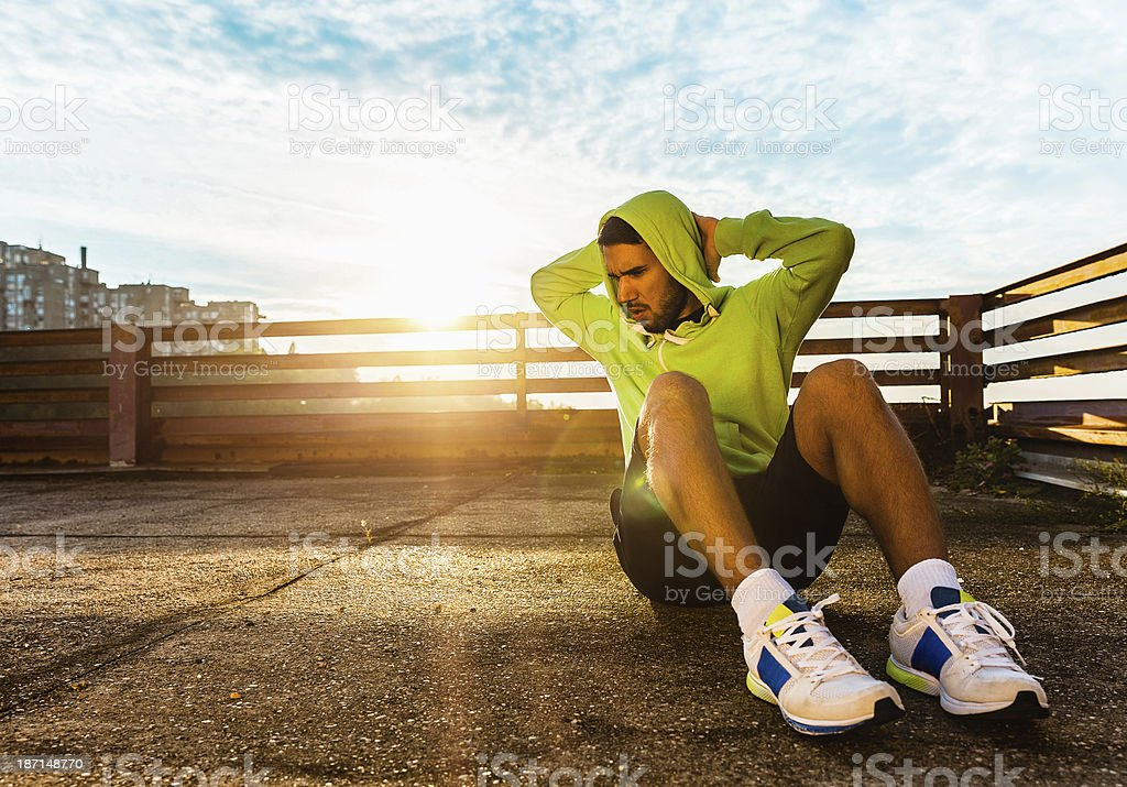 Photo of a young man exercising doing sit ups outdoors stock photo