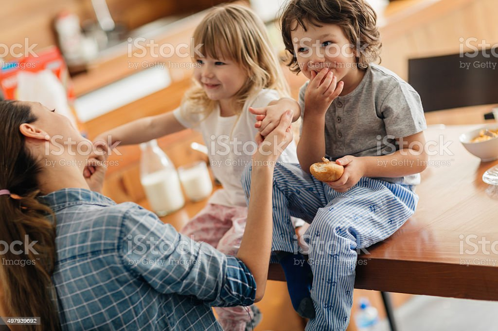 Photo of a young mother and her children having breakfast stock photo