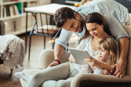 871175856 istock photo Photo of a young smiling family sitting with tablet 468272446